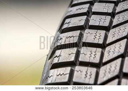 Close up detail part of new black rubber car tire protector, selective focus, on light blurred copy space background. Transportation, safety, reliability concept. stock photo