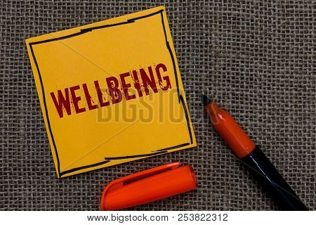 Conceptual hand writing showing Wellbeing. Business photo showcasing A good or satisfactory condition of existence including health Orange paper Marker Communicate ideas Jute background. stock photo