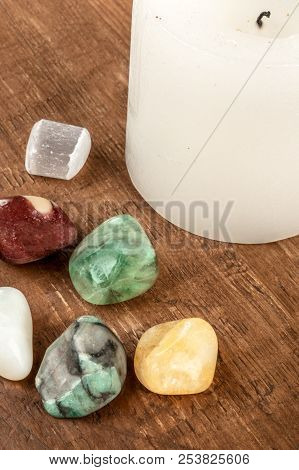 Semiprecious gemstones on a dark wooden background with a white candle. Emerald, selenite, jasper, citrine, opal, jade, fluorite stock photo