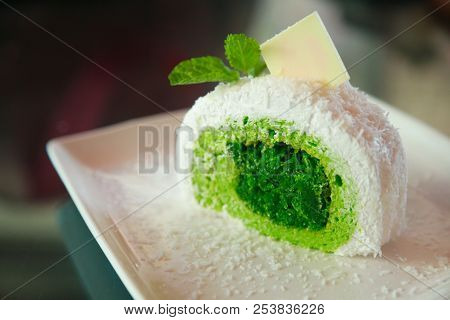white tropical coconut cake with green pandan flavor on shredded coconut filling, topped  mint leaves and white chocolate, Asian sweet delight fruit snack dessert, summer food collection concept stock photo