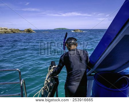 Asian traveler dive on the boat with idyllic ocean and blue sky in vacation time,Summer concept stock photo