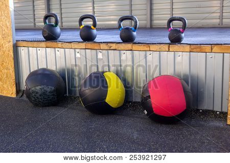 Iron dumbbells of different weights with multi-colored handles stand in the gym on a rubber mat. Medical balls of black and red are arranged in a row on the floor. Close-up of contrast sports equipmen stock photo