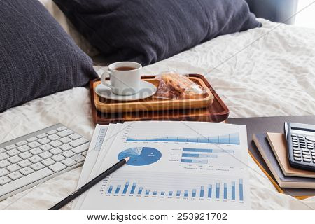 Pencil on blue chart, graph analysis, documents, keyboard, books, calculator, tea break on wrinked duvet and bed. Natural daylight, pillows, cushions, on background. Concept of freelance work at home. stock photo
