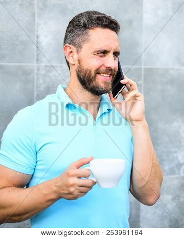 Man drink cappuccino speak phone grey wall background. Coffee can be endlessly reimagined make something old new again like entrepreneurs craft and reinvent businesses. Pleasant coffee break at work stock photo