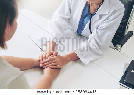 Woman doctor holds patient hand patient in room of hospital office. Healthcare and medical service. stock photo