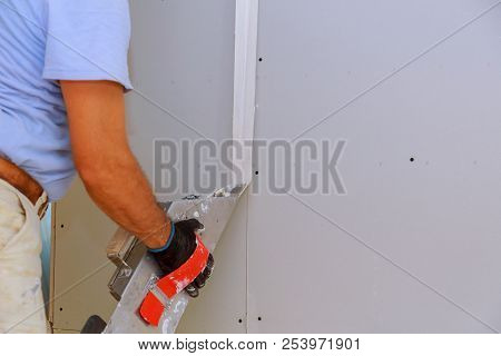 Worker working with putty and spatula work aligns with wall stock photo