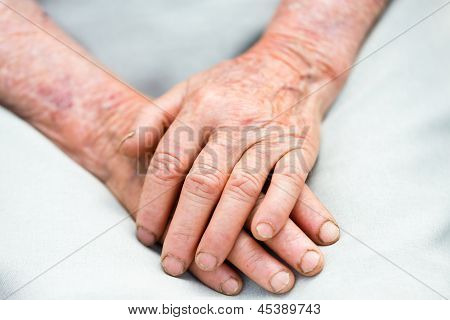 Two elderly hands representing the passing of time. stock photo