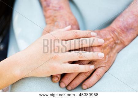 Caring woman hands over elderly hands being concept of trust and reliability. stock photo