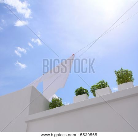 Clean laundry air drying on a clothing line in a blue sky and pots with green plants stock photo