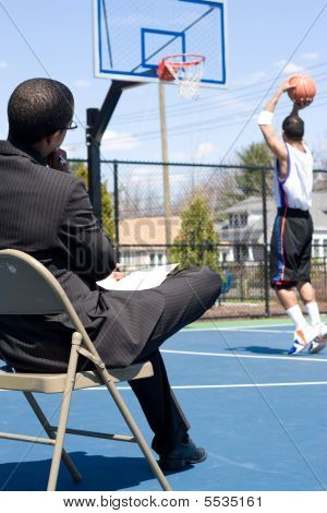 A basketball coach in a business suit observing a player on the team. He could be also be recruiter trying to scout him. stock photo