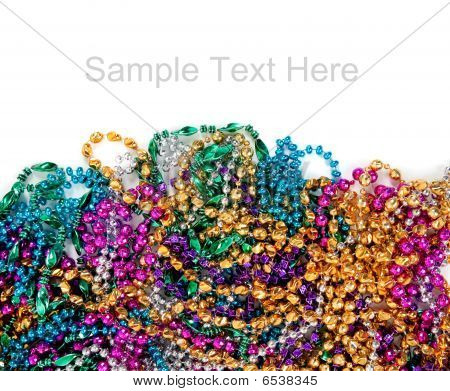 Multi colored mardi gras beads including blue green purple pink yellow and gold on a white background with copy space stock photo