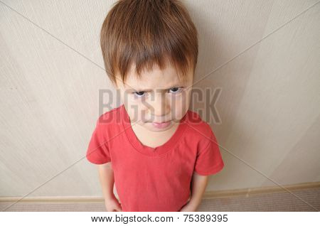 resentful angry cute boy looking from below stock photo