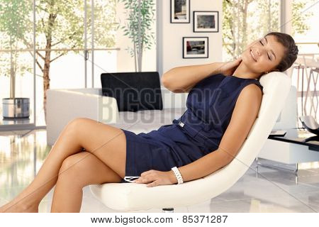 Attractive young brunette caucasian woman in blue dress resting in leather chair at trendy home. Smiling, caressing herself, eyes closed, relaxing. stock photo