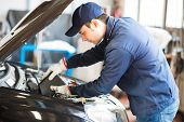 Portrait of an auto repairman placing oil in an auto motor