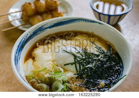 Japanese traditional style ramen soba noodle soup with rice balls on a stick and green tea on the background stock photo