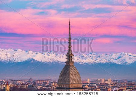 Torino (Turin Italy): cityscape at sunrise with details of the Mole Antonelliana towering over the city. Scenic colorful light on the snowcapped Alps in the background. stock photo