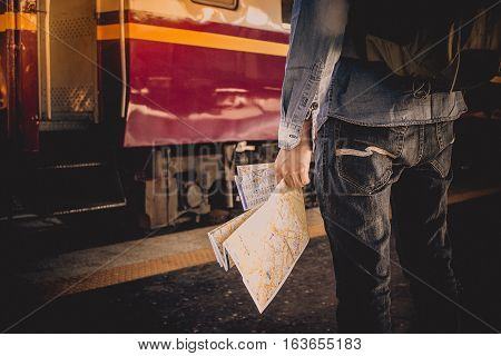 Young man holding map standing on platform at train station for travel. Travel concept by train. stock photo
