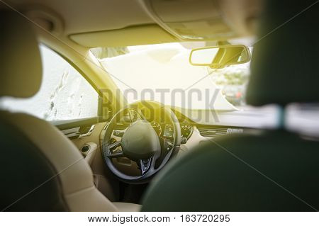 Elegant woman cleaning the car windshield from snow after a snow storm - view from inside the car stock photo