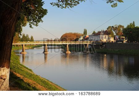 View on the main bridge across the river Uzh in Uzhhorod in warm sunset light. High tree grows on the left stock photo
