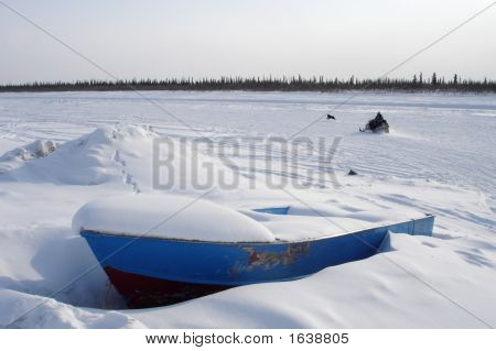 A snowmobiler runs his dog next to the winter ice road on the east channel of the Mackenzie River near Inuvik Northwest Territories. A boat waits for the spring thaw.  stock photo