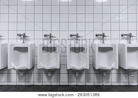 Clean male toilet row of urinals in a public restroom black and white stock photo