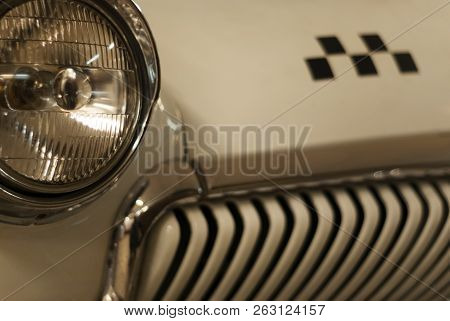 fragment of the front part of a vintage taxi car, focus on the headlight, checker emblem and radiator in blur stock photo