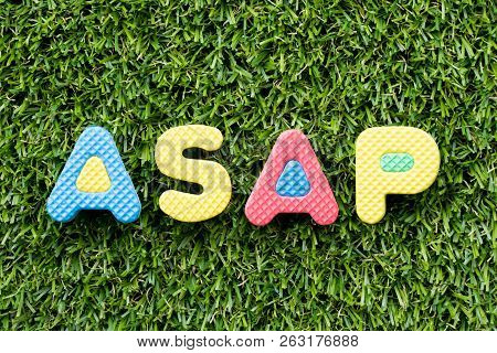 Color alphabet letter in word ASAP (Abbreviation of as soon as possible) on artificial green grass background stock photo