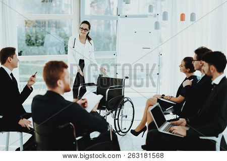 Presents New Wheelchair. Group Disabled Worker. Workers with Disabilities. People with Limited Opportunities. Business Meeting. White Coat. Business Suits. Discuss Work Concept. Man in Wheelchair. stock photo