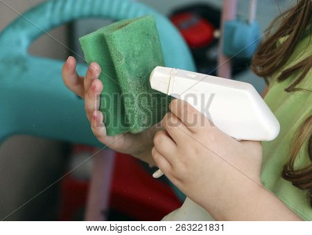 the baby is doing wet cleaning. sprinkles washing liquid onto  sponge from a plastic bottle. stock photo
