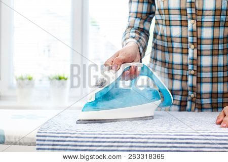 Womans hands holding hot iron, steaming clothes stock photo