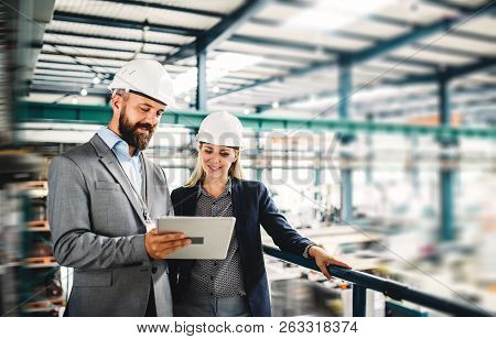A Portrait Of An Industrial Man And Woman Engineer With Tablet In A Factory, Working.