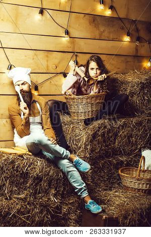 Funny man chef cook or baker with beard and moustache in hat toque and cute girl cookee teenager in apron sit on straw bales on rustic background. stock photo