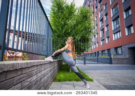 Young woman gymnast with a slim figure in sportswear doing stretching on a city street on a warm summer day. Stretching in the open air stock photo