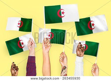 Hands waving flags of Algeria stock photo