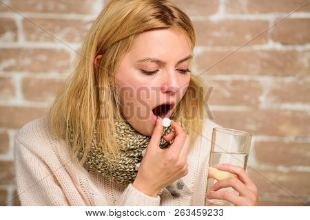 Woman tousled hair scarf hold glass water and tablets blister. Girl feels ill suffer fever and take medicine. Pills for breaking fever. Take medications to reduce fever. Headache and fever remedies stock photo