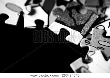 Pieces of children's puzzles scattered on a dark background close up. Black and white stock photo
