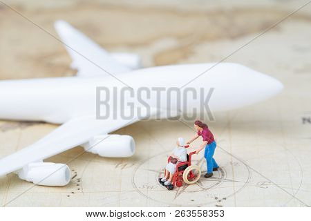 Medical trip planning or travel concept, miniature senior elderly people on wheelchair with son or caregiver standing with toy airplane on vintage world map with compass, next destination. stock photo