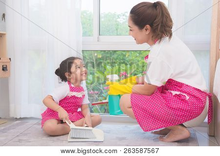 Asian mother teaching daughter cleaning their home . Family housework concept. stock photo