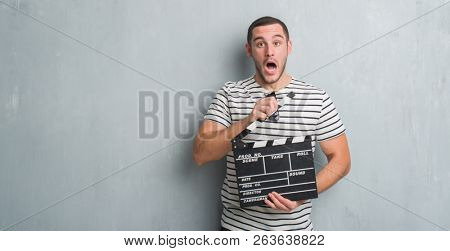 Young caucasian man over grey grunge wall holding movie clapboard scared in shock with a surprise face, afraid and excited with fear expression stock photo