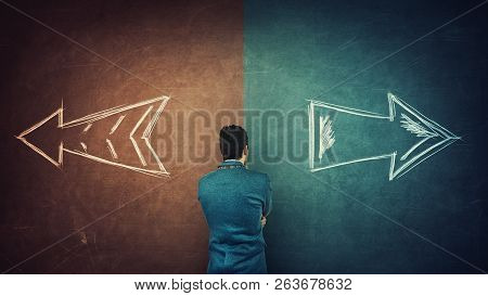 Puzzled Businessman And A Split Blackboard With Arrows Going In Two Different Ways Red And Blue Side