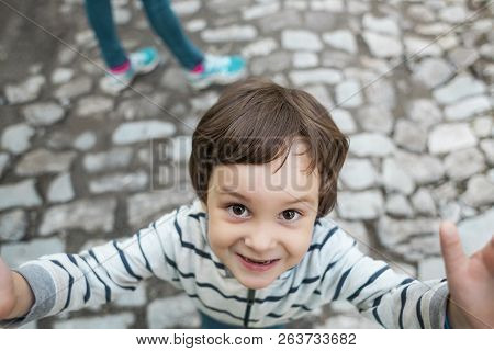 The child looks up. Portrait of a little boy. The kid walks along the city street. Cute little boy is smiling. stock photo