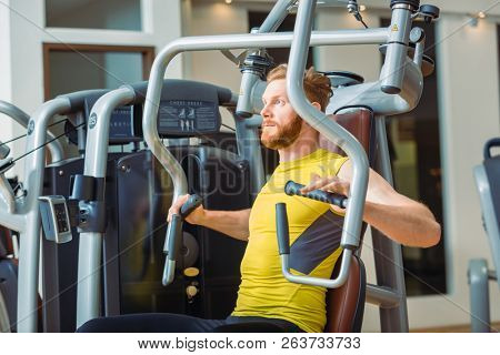 Portrait of a handsome bodybuilder smiling and looking at camera while exercising at a modern fitness machine for pectoral fly and deltoid workout stock photo