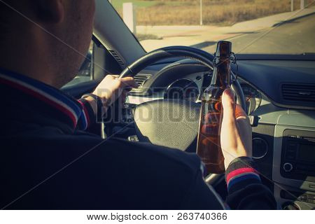 A drunken man driving a car with a bottle of alcohol in his hand.A man holds a driving wheel and a bottle of beer. stock photo