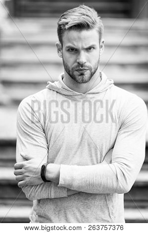 Handsome in style. Man unshaven folded arms looks handsome and cool. Guy bearded attractive cares about appearance. Man bristle serious face, urban background, defocused. Metrosexual concept. stock photo