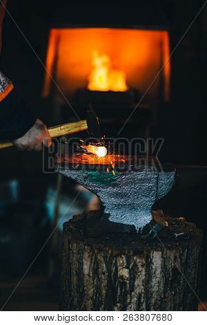 Blacksmith workshop. The blacksmith works on the anvil with a hot metal billet stock photo