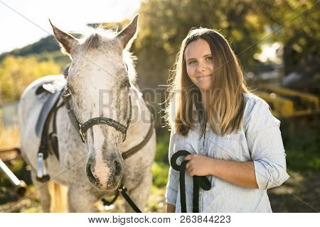 A Beautiful teen girl on the farm with her horse. stock photo