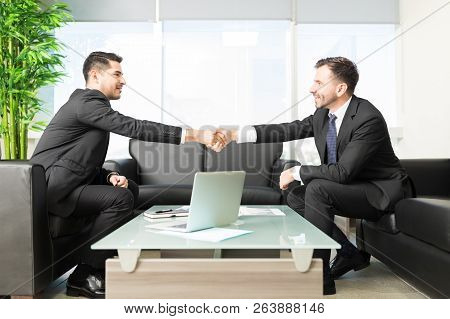 Business people shaking hands after closing deal in office stock photo