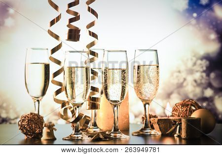champagne glasses against holiday lights ready for New Year's eve party