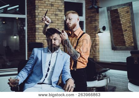 Hair Preparation is just for dashing chap. Bearded stylish barber shop client. Bearded client visiting barber shop. Barber scissors. Beard styling and cut. Making haircut look perfect in barber shop stock photo