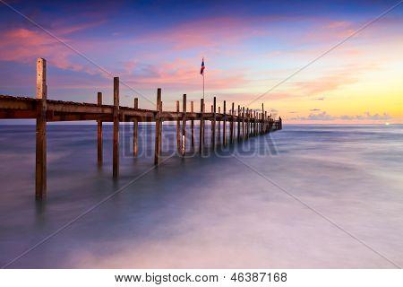 Pont sur la plage au coucher du soleil et mer vague